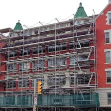 Scaffolding installed in front of red building